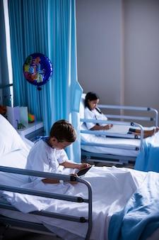 Pazienti con tavoletta digitale e libro seduto sul letto