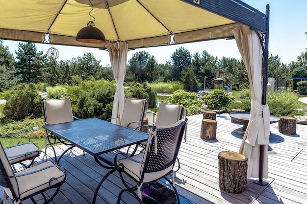 Patio con tavolo e sedie sotto tettoia e area barbecue in tenuta di campagna