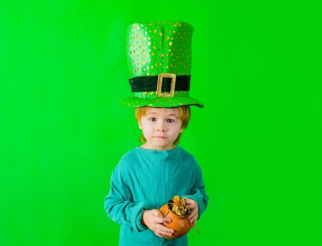 Il ragazzo con il cappello a cilindro verde del giorno di san patrizio con il cappello verde tiene la pentola con il leprecauno d'oro verde leprecauno verde