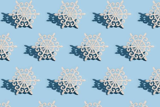 Modello di decorazione per albero di natale sotto forma di fiocchi di neve su sfondo blu: concetto minimalista di nuovo anno
