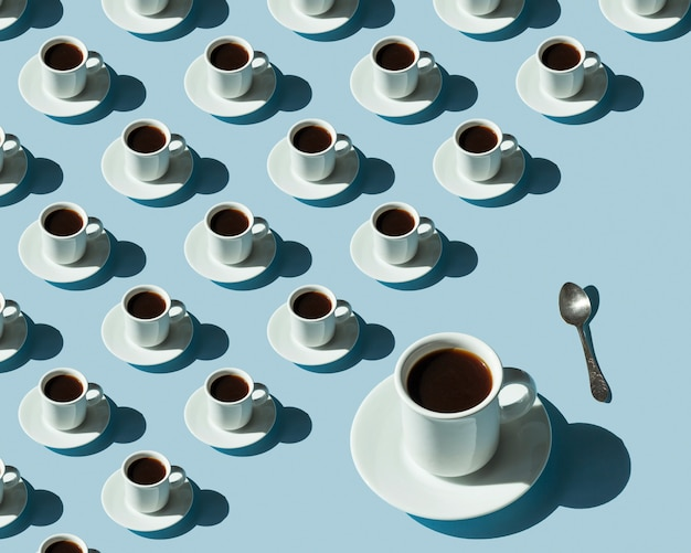Modello di tazze con caffè e uno grande su una superficie blu