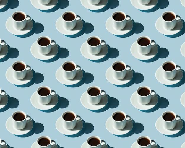 Modello di tazze con caffè su una superficie blu