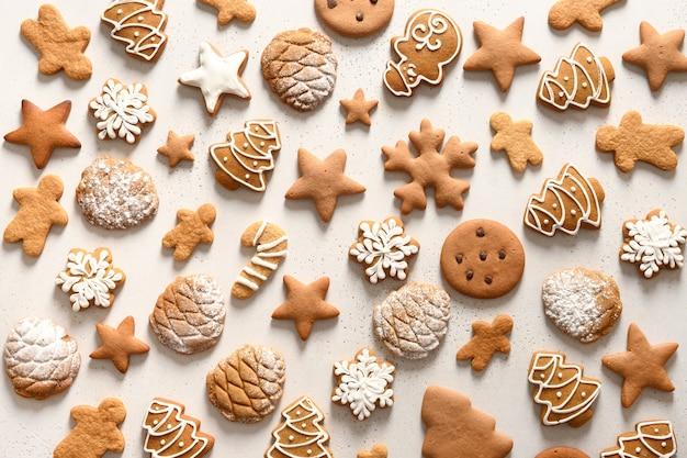 Modello di diversi biscotti di panpepato fatti in casa di natale come fiocchi di neve, stelle, albero di natale su sfondo bianco. natale sfondo astratto.