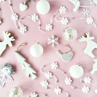 Modello fatto di decorazioni natalizie bianche con palline di vetro natalizie, orpelli, fiocco, alci, uccelli su sfondo rosa.