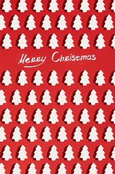 Modello fatto di decorazioni natalizie bianche con albero di natale su sfondo rosso. carta da parati di natale. disposizione piatta, vista dall'alto