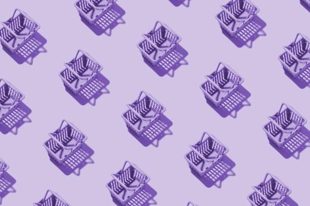 Modello cestino della spesa in miniatura in un supermercato in tinta viola. concetto minimalista dello shopping dello spazio della copia.
