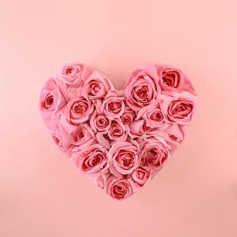 Un motivo di fiori di rose rosa disposti a forma di cuore su uno sfondo rosa primavera estiva