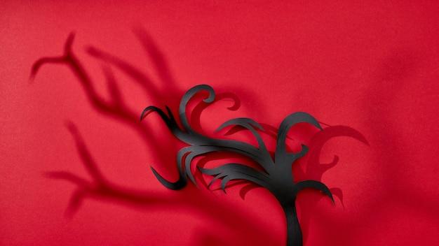 Modello di ombre e ramo di carta nera fatta a mano su uno sfondo rosso con spazio per il testo. carta di halloween. lay piatto