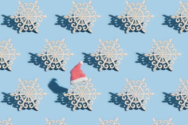 Un modello di fiocchi di neve, uno dei quali indossa un cappello da babbo natale, su sfondo blu: diverso concetto di capodanno
