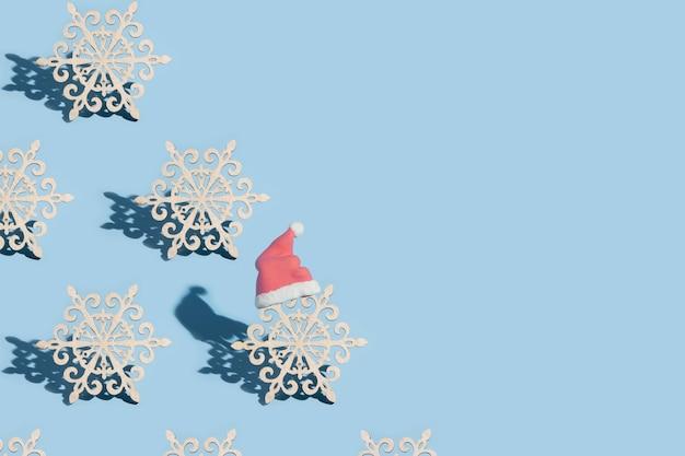 Un modello di fiocchi di neve, uno dei quali indossa un cappello da babbo natale, su uno sfondo blu con spazio di copia