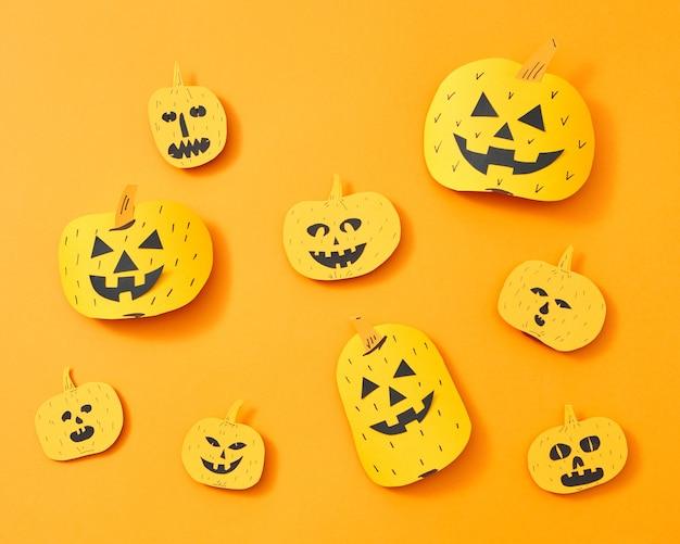 Modello di una varietà di zucche di carta artigianali con facce su uno sfondo arancione con spazio per il testo. layout per halloween. lay piatto