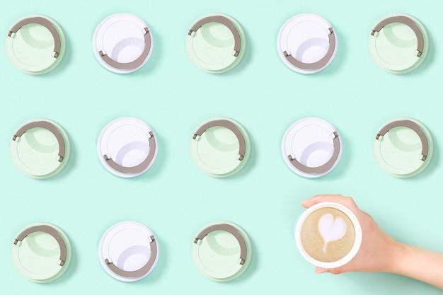 Modello con cappuccino da asporto e latte art in tazza termica eco riutilizzabile.