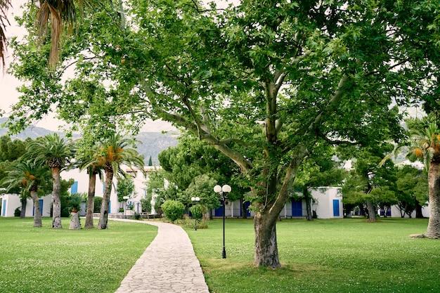 Il sentiero lastricato conduce attraverso un prato verde con alberi e lanterne alla casa