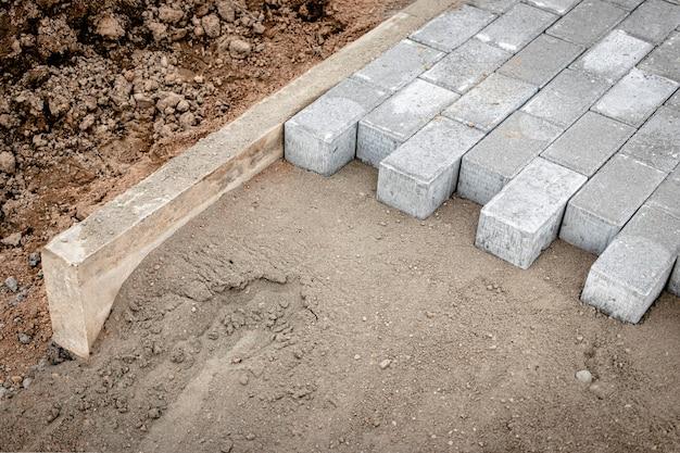 Riparazione della pavimentazione e posa di lastre per pavimentazione sulla passerella, cubetti di piastrelle impilate sullo sfondo. posa di lastre per pavimentazione nella zona pedonale della città, riempimento di sabbia. piastrelle stradali e cordoli.