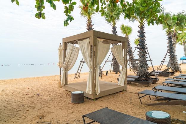 Padiglione sulla spiaggia con il mare in una giornata nuvolosa - concetto di viaggio e vacanza