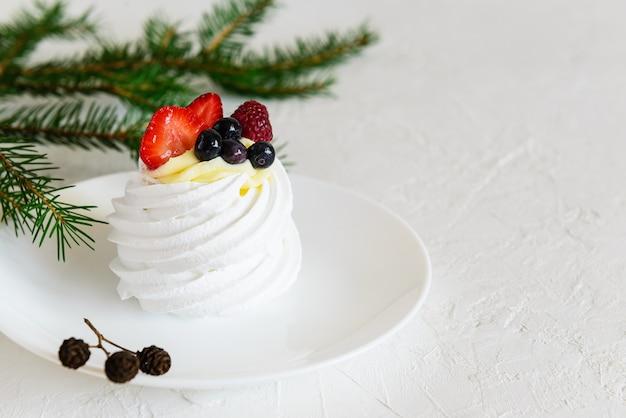 Torta pavlova con frutti di bosco e un ramo di abete rosso su un tavolo bianco. orientamento orizzontale, copia dello spazio.