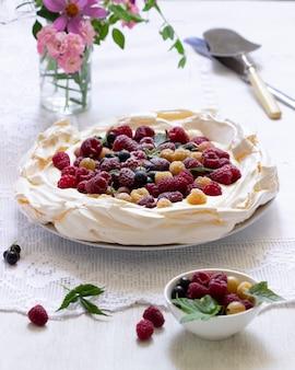 Torta pavlova con panna e frutti di bosco e bouquet di fiori su fondo chiaro.