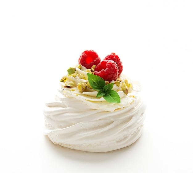 Pavlova torta da dessert con panna e lamponi freschi su un muro bianco, close-up Foto Premium