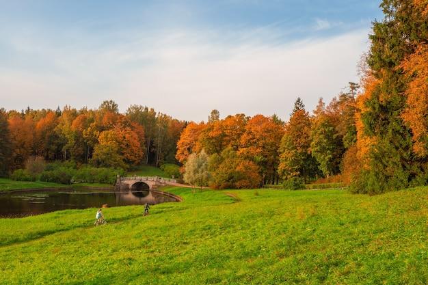 Parco d'autunno pavlovsky. un paio di ciclisti sul sentiero. fiume slavyanka a pavlovsk, san pietroburgo, russia