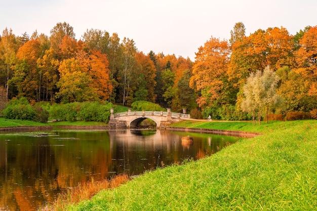 Parco d'autunno pavlovsky. un ciclista sul sentiero. fiume slavyanka a pavlovsk, san pietroburgo, russia