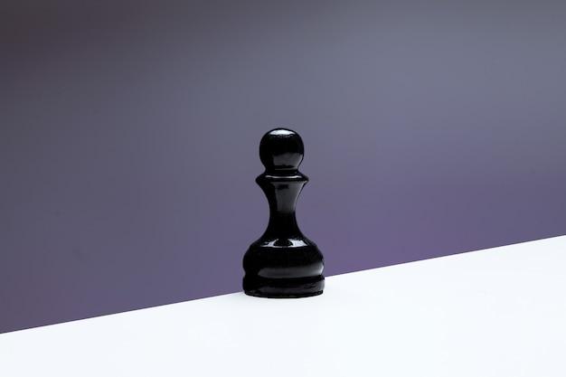 Pedone sul bordo del tavolo concetto di solitudine vecchio pezzo degli scacchi in legno colore nero