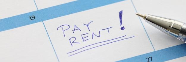 Pagare l'affitto è scritto sul foglio di calendario con il primo piano della penna a sfera. promemoria note adesive concetto