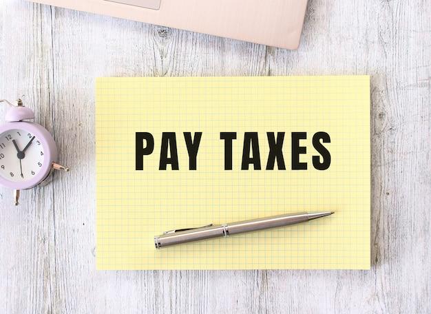 Pagare le tasse testo scritto in un taccuino che giace su un tavolo da lavoro in legno accanto a un computer portatile. concetto di affari.