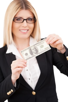 Giorno di paga! fiduciosa imprenditrice matura che allunga le mani con una banconota da cento dollari e sorride mentre sta in piedi isolato su bianco