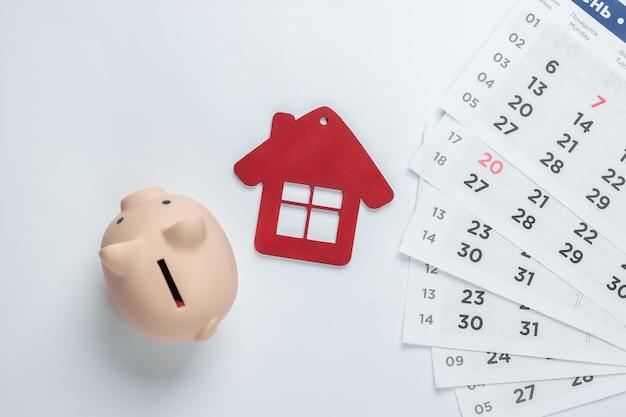 Pagare gli affitti per le abitazioni. salvadanaio, statuina casa con calendario mensile. vista dall'alto