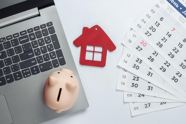 Pagare gli affitti per un alloggio o cercare un alloggio online. computer portatile con salvadanaio, statuetta di casa con calendario mensile. vista dall'alto