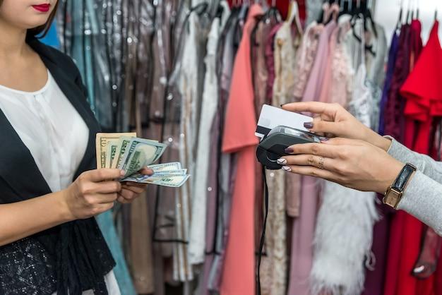 Pagamento in negozio di abbigliamento con carta e banconote in dollari