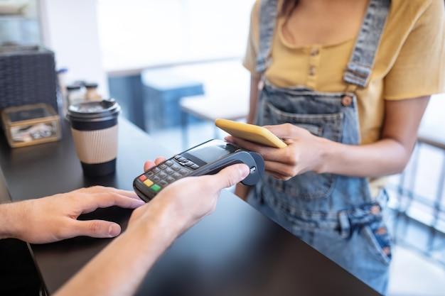 Ordine di pagamento. mani sottili femminili che tengono smartphone giallo vicino al poster sul bancone nella caffetteria