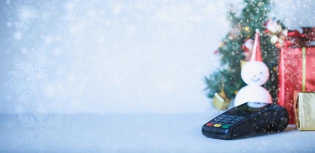 Terminale di pagamento con carta di credito e regalo con sfondo albero di natale. concetto di vendita di natale