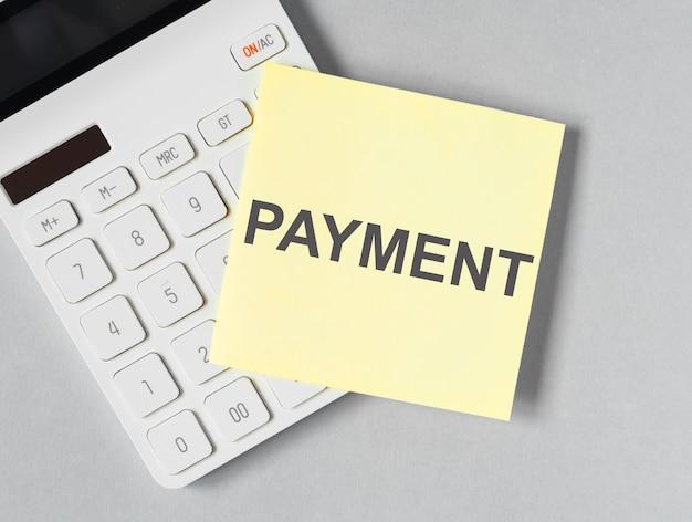 Parola di pagamento, iscrizione. concetto finanziario aziendale, promemoria su una nota adesiva sulla calcolatrice.