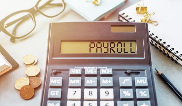Parola di libro paga scritta sulla calcolatrice. business e concetto finanziario
