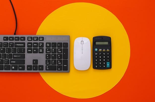 Tastiera pc e calcolatrice su arancione con cerchio giallo
