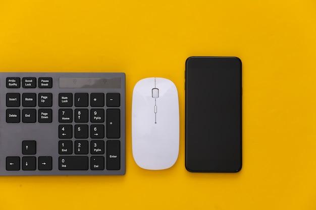 Tastiera per pc con mouse per pc, smartphone su giallo