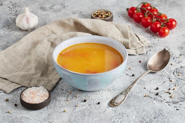 Zuppa di piselli in una ciotola con cucchiaio, pomodori, sale e panno da cucina su fondo di marmo chiaro