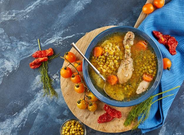 Zuppa di piselli con pollo, carote, pomodori ed erbe aromatiche in un piatto fondo su tavola di legno con tovagliolo. disposizione piatta.