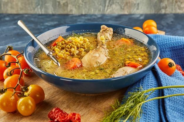 Zuppa di piselli con pollo, carote, pomodori ed erbe aromatiche in un piatto fondo su tavola di legno con tovagliolo.