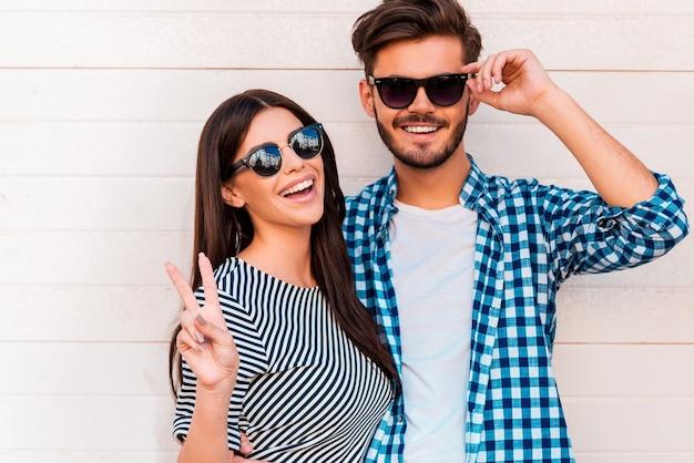 Pace fuori! felice giovane coppia di innamorati che guarda l'obbiettivo e sorride mentre sta in piedi all'aperto
