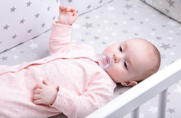 Bambino pacifico che si trova su un letto bianco, vista superiore