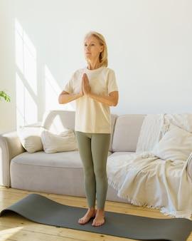 Donna matura pacifica che medita mentre pratica yoga sulla stuoia a casa