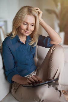 Donna matura pacifica che sorride facendo uso del pc della compressa digitale mentre si rilassa su un sofà a casa nel