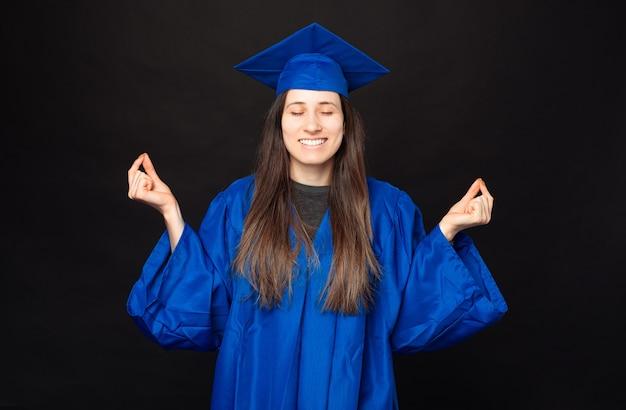 Donna giovane studentessa pacifica che indossa bachelor e cappello di laurea e che fa gesto zen