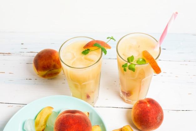 Cocktail rinfrescante di succo d'arancia freddo alla pesca in un bicchiere con ghiaccio e pezzi di frutta e menta in estate.