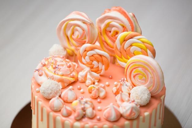 Torta color pesca con meringa, caramelle, macchie di cioccolato e gelatine