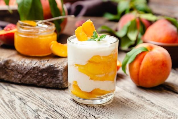 Dessert di frutta alla pesca in tazza di vetro su tavola in legno rustico con frutta fresca di pesca, marmellata di pesche dolce fatto in casa con frutta. macedonia di frutta con yogurt o panna acida.