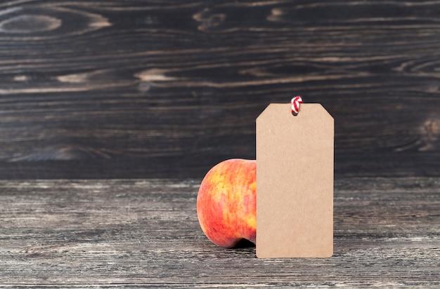 Pesche su uno sfondo scuro con un'etichetta di carta per la scrittura, l'etichetta è realizzata con carta riciclata