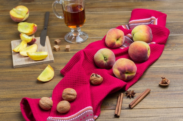 Pesche e noci sul tovagliolo rosso. pesche affettate e coltello a bordo. bicchiere di tè, bastoncini di cannella e anice stellato sul tavolo.